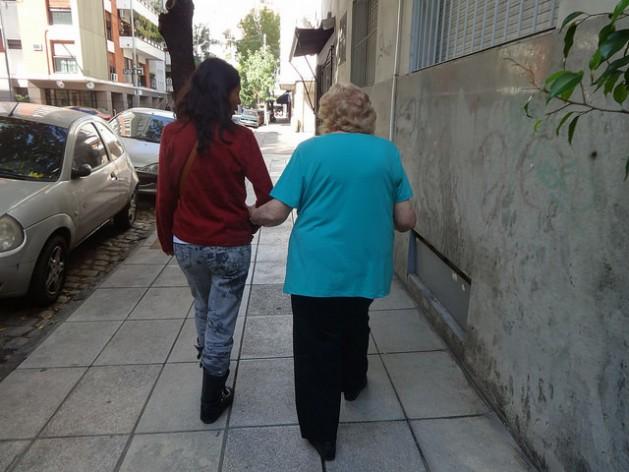 Uma idosa se apoia em uma cuidadora, em uma rua do bairro Norte, de Buenos Aires, na Argentina. Foto: Fabiana Frayssinet/IPS